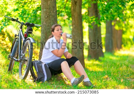 young woman with bottle of water resting near a tree - stock photo