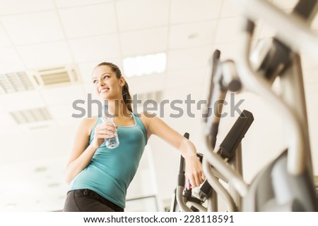 Young woman with bottle of water training in the gym - stock photo
