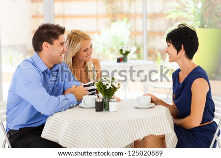 young woman with boyfriend meeting future mother in law in cafe - stock photo