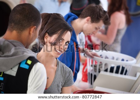 Young woman with boyfriend smiles in laundromat - stock photo