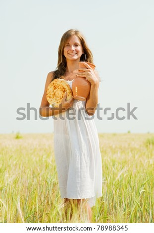 Young woman  with bread at cereals field in summer - stock photo