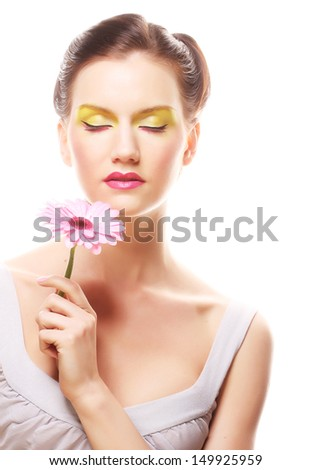 Young woman with bright make up holding pink gerber - stock photo