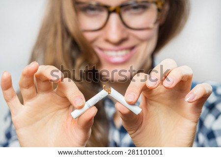 Young woman with broken cigarette. Stop smoking concept. focus on cigarette and hands - stock photo