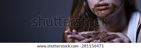 Young woman with bulimia nervosa eating chocolate - stock photo