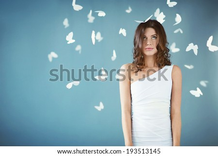 Young woman with butterflies in studio - stock photo