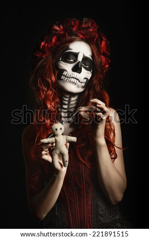 Young woman with calavera makeup (sugar skull) piercing a voodoo doll - stock photo