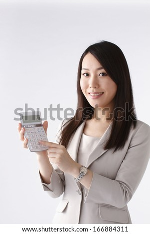 Young woman with calculator - stock photo