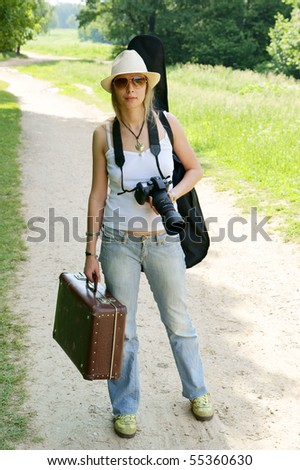 Young woman with camera and suitcase on the road - stock photo