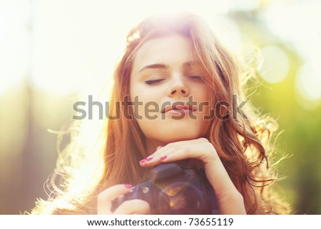 Young woman with camera outdoors portrait. Soft sunny colors. - stock photo
