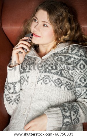 young woman with cell phone relaxing on a couch - stock photo