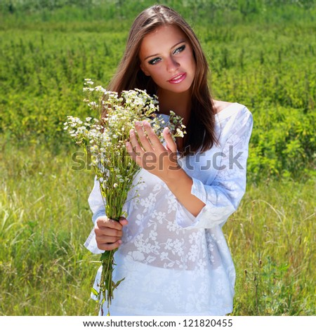 Young woman with chamomile bouquet - stock photo