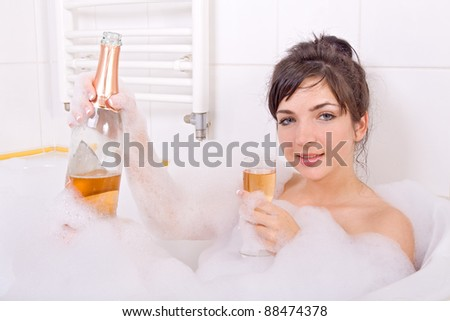 Young woman with champagne in the bathtub