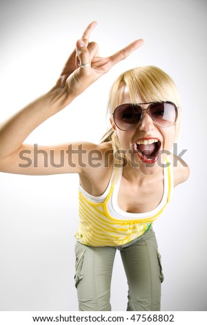 Young woman with characteristic heavy metal hand gesture - stock photo