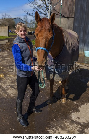 Young woman with Chestnut stallion horse at Riding Stable.