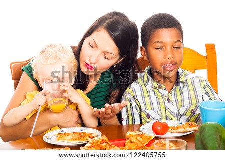 Young woman with children eating pizza and drinking juice, isolated on white background. - stock photo