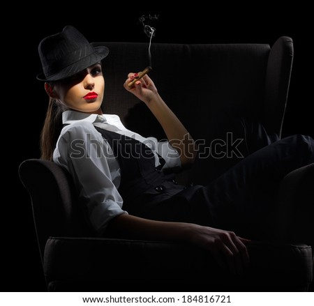 Young woman with cigar sit on chair on black - stock photo