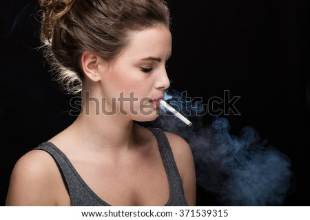 young woman with cigarette, smoking concept on black background - stock photo