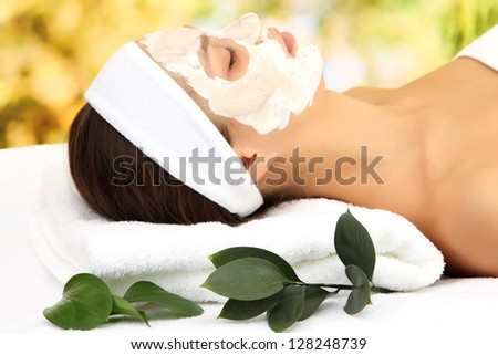 Young woman with clay facial mask, on bright background - stock photo