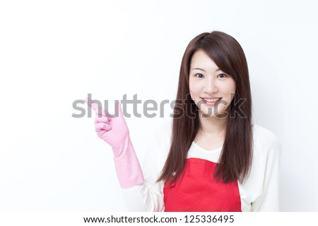 young woman with cleaning gloves pointing copy space - stock photo