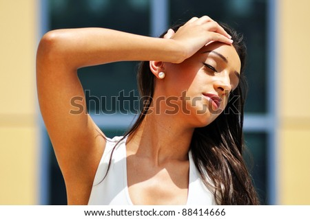 Young woman with closed eyes and her hand on the head