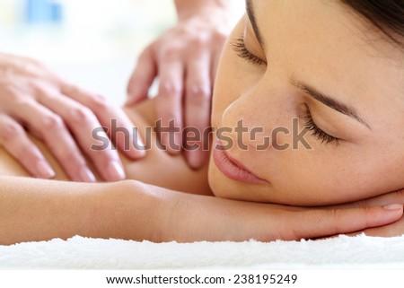 Young woman with closed eyes enjoying massage - stock photo