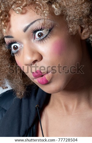 Young woman with clown make-up and wig looking surprised and intrigued, eyes wide open