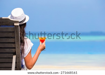Young woman with cocktail glass near swimming pool - stock photo