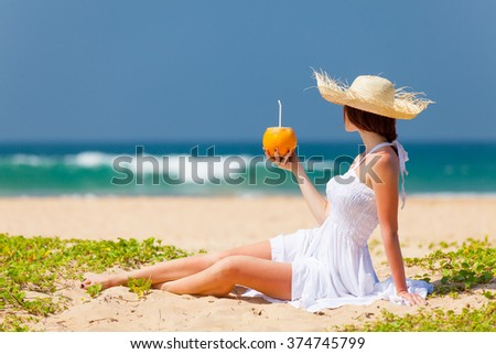 Young woman with coconut cocktail near the sea. Back side view