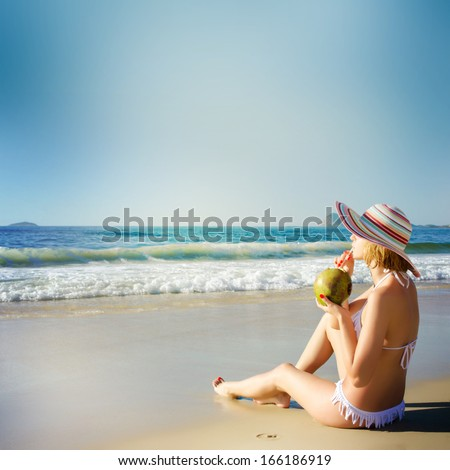 Young woman with coconut cocktail on the beach - stock photo