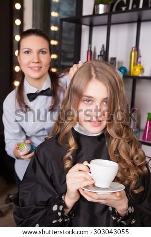 Young woman with coffee cup and hairdresser holding hairspray - stock photo