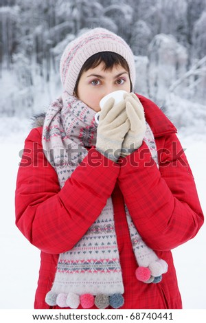 Young woman with coffee cup in winter - stock photo