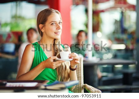 young woman with coffee in restaurant outdoors - stock photo