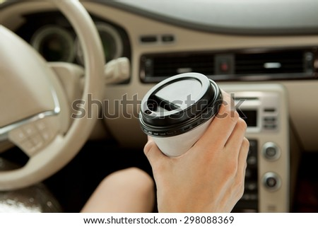 Young woman with coffee to go driving her car  - stock photo