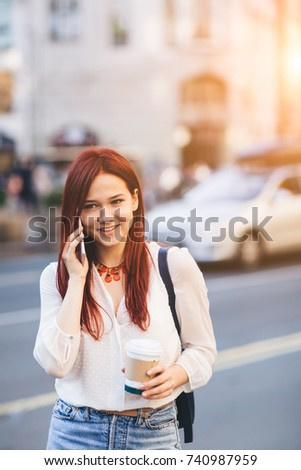 Young woman with coffee to go standing at the street and talking on mobile phone