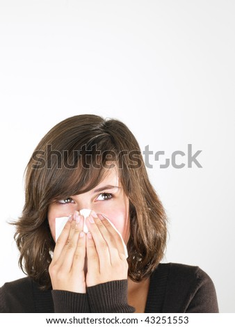 Young woman with cold blowing nose. Vertically framed shot. - stock photo