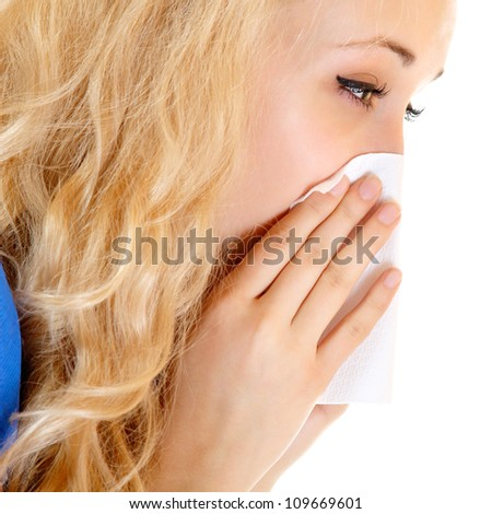 Young woman with cold sneezing into tissue over white background - stock photo