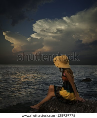 Young woman with colorful dress and hat sits on rocky shore with storm on the horizon. - stock photo