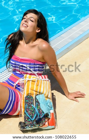Young woman with colorful dress lying, sunbathing and laughing at poolside on blue water background. Hot summer day.