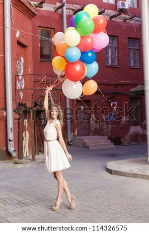 Young woman with colorful latex balloons, urban scene, outdoors - stock photo