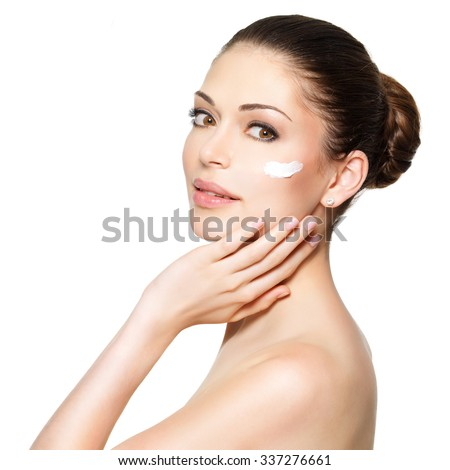 Young woman with cosmetic  cream on a clean fresh face. Skin care concept - stock photo