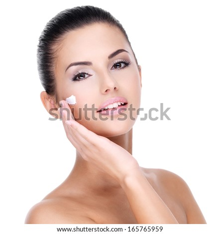 Young woman with cosmetic  cream on a pretty fresh face - isolated on white - stock photo