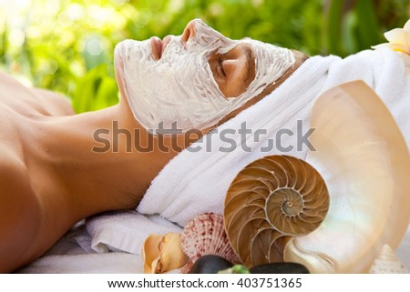 young woman with cosmetic mask on face and towel on a head is relaxing in spa clinic. Background with leaves