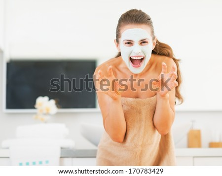 Young woman with cosmetic mask on face scaring - stock photo