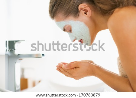 Young woman with cosmetic mask on face washing