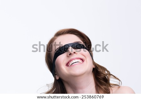 Young woman with covered eyes looking at copyspace - stock photo