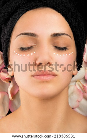 Young woman with cream around the eyes.  - stock photo