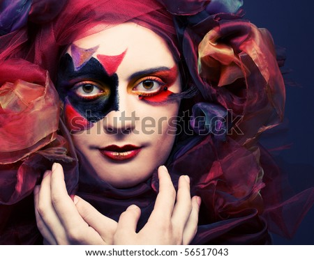Young woman with creative make-up and in exotic hat - stock photo
