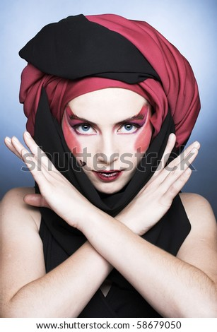 Young woman with creative make-up in black and red turban