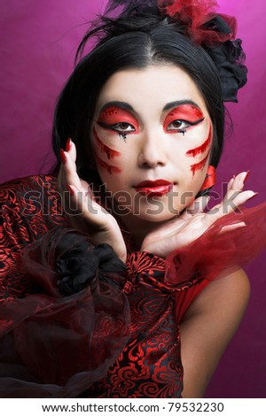 Young  woman with creative make-up in red tones - stock photo