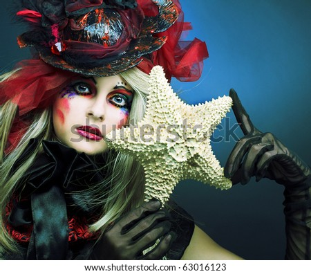 Young woman with creative make-up with sea-star in her hands